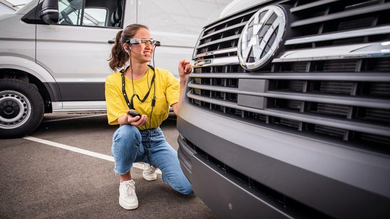 Die Livebratung kniet vor einem Modell von Volkswagen Nutzfahrzeuge.