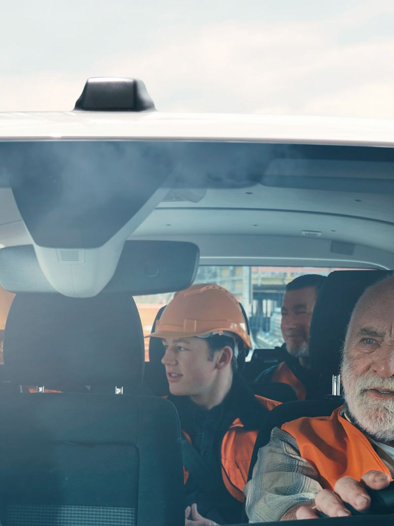 Bauarbeiter sitzen in Inneren eines VW Transporters und unterhalten sich während der Fahrt.