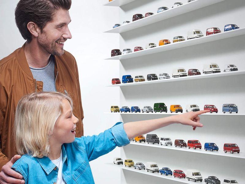 Ein Mann und ein Kind stehen an einem Regal das mit Volkswagen Modell Autos bestückt ist.