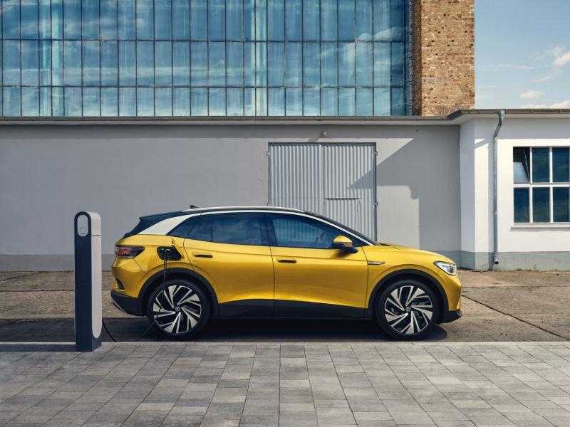 Ein gelber Volkswagen ID.4 steht vor einem Haus an einer Ladestation.