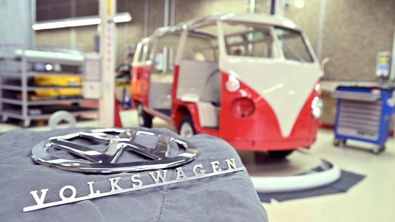 Die lackierte Karosserie eines Volkswagen T1 und das VW-Emblem.