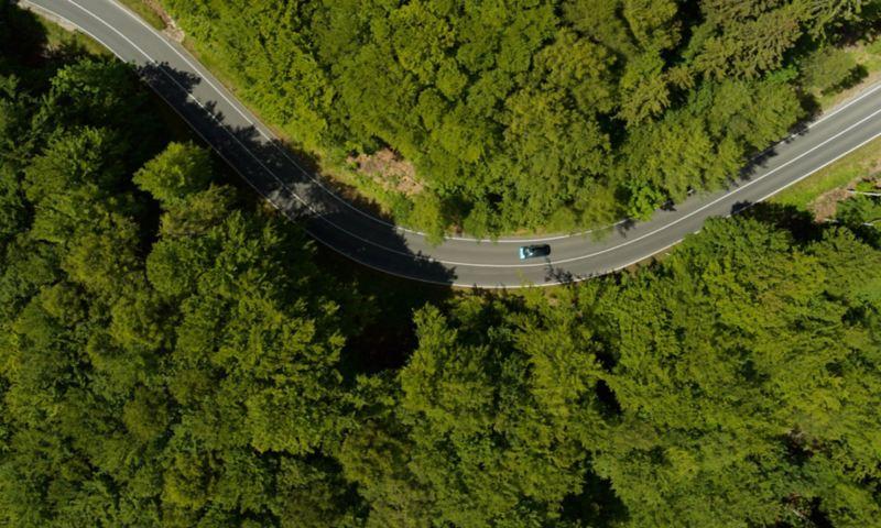 Αεροφωτογραφία : Ενα αυτοκίνητο Volkswagen οδηγεί σε δρόμο μέσα σε ένα δάσος