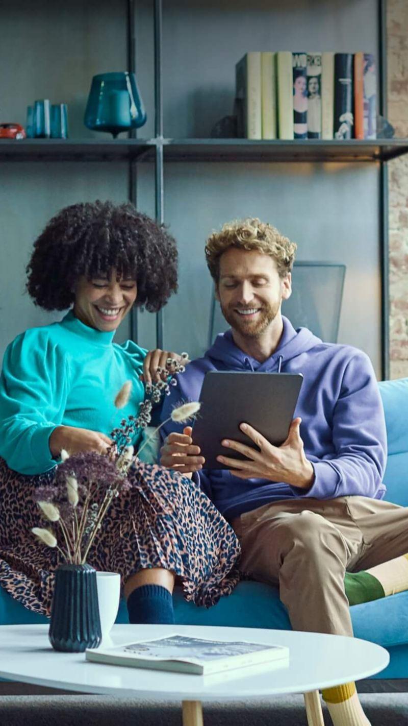 Ein Mann und eine Frau sitzen auf einer Couch und gucken einen Laptop Bildschirm an.