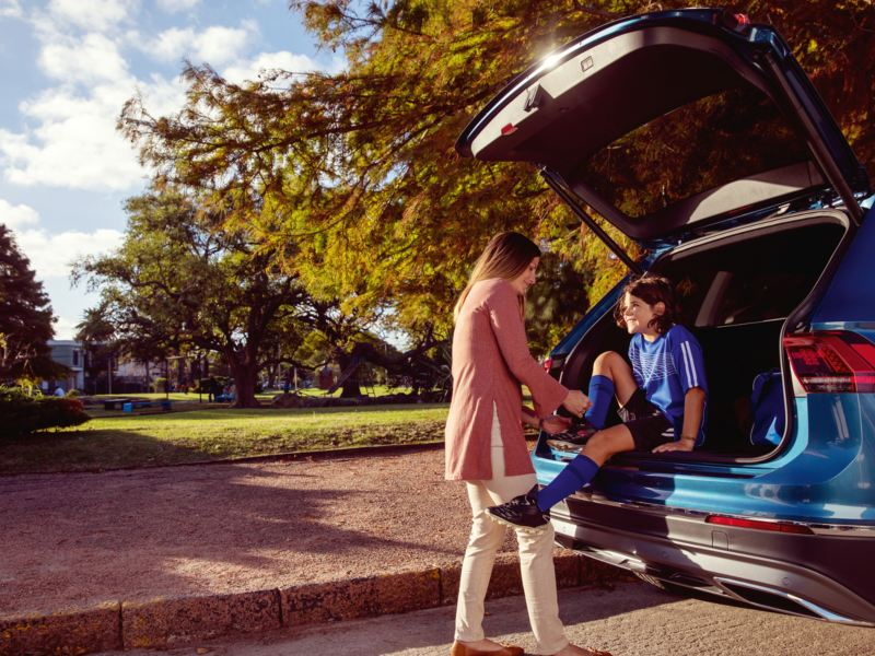 A young girl sitting in the trunk of VW SUV while her mom helps to tie a shoe, outgoing link to volkswagenplus.ca/en