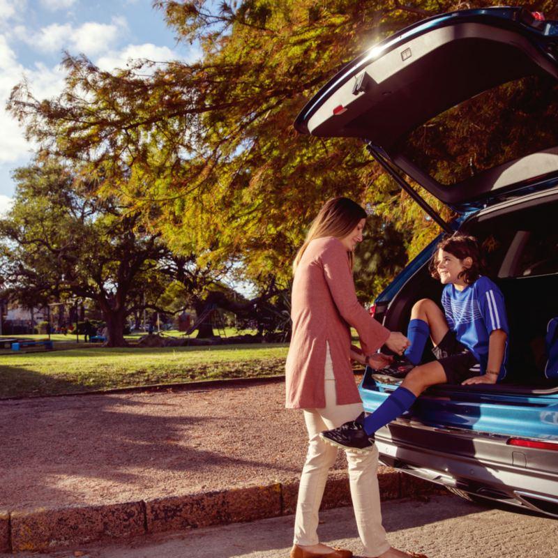 Jeune fille assise dans le coffre d'un VUS VW pendant que sa mère aide à lacer sa chaussure, lien vers volkswagenplus.ca/fr
