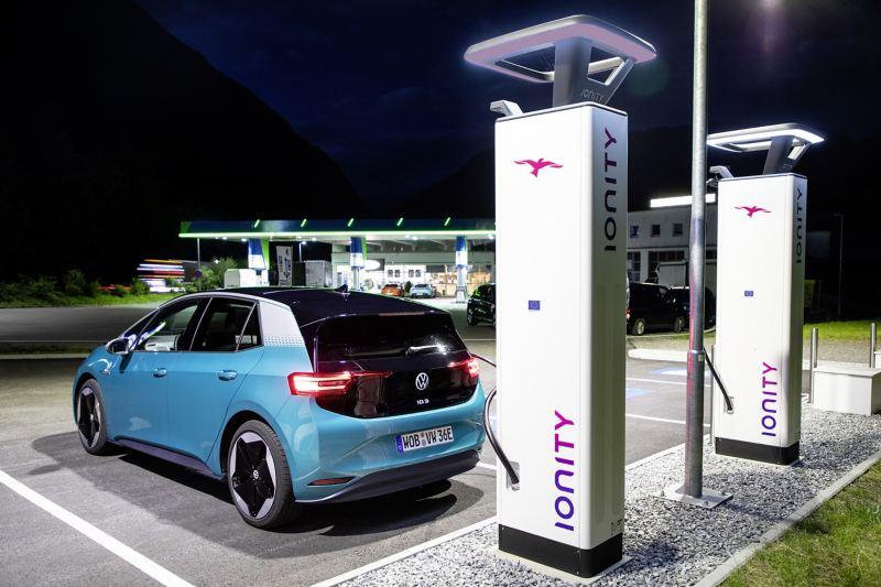 Ein VW ID.3 (Stromverbrauch kombiniert: 15,4–13,1 kWh/100 km (NEFZ); CO2-Emission kombiniert: 0 g/km; Effizienzklasse: A+) wird an einer Schnelladestation geladen. Im Hintergrund ist eine herkömmliche Benzin-Tankstelle zu sehen.