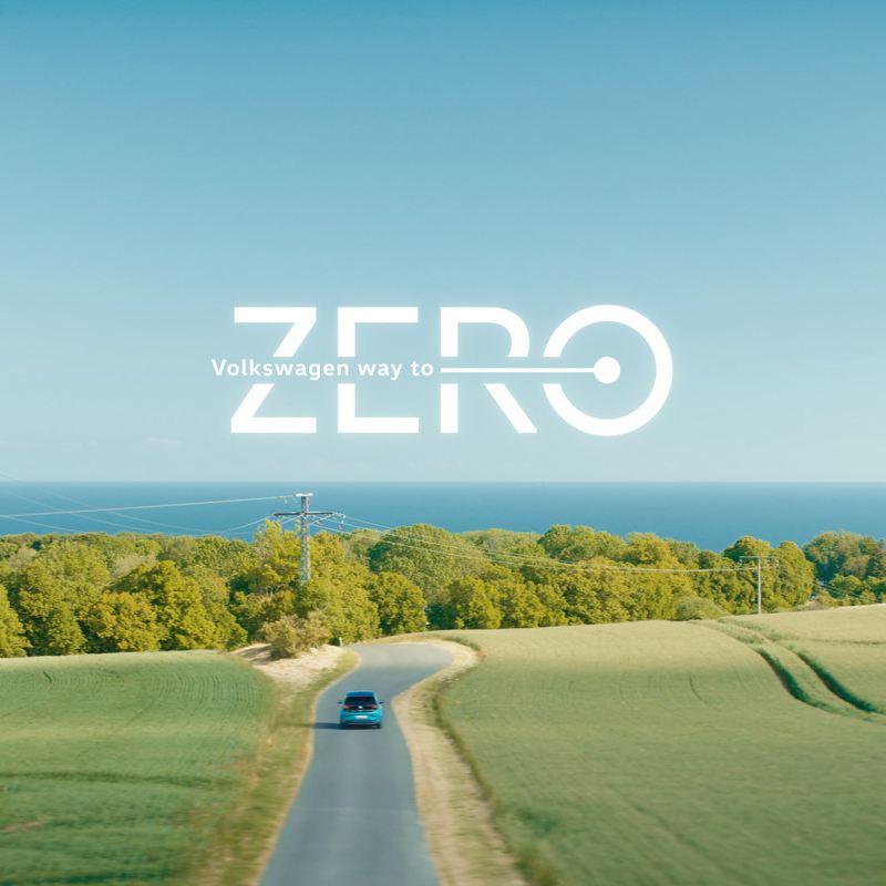 Una Volkswagen ID.3 percorre su strada e il logo Way to Zero in risalto