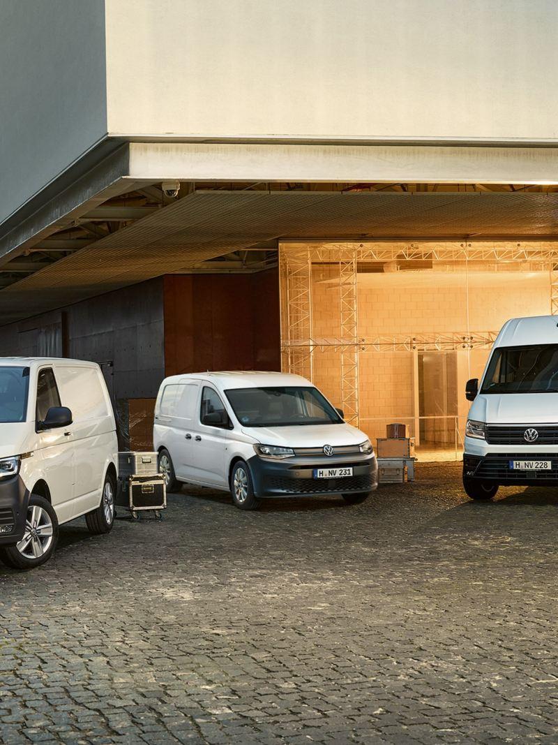 Ein VW Caddy, VW Transporter und VW Crafter vor einem Veranstaltungsgebäude.