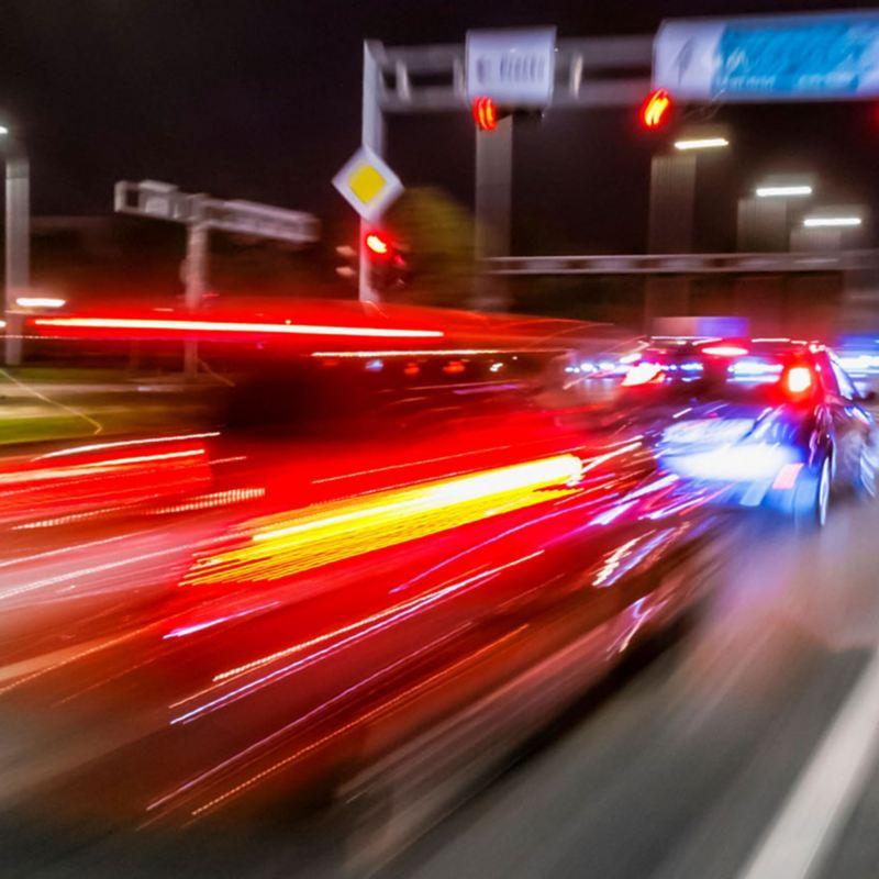 Ein Auto bremst bei Nacht an einer roten Ampel. Bewegungsunschärfe lässt die Rücklichter Streifen ziehen