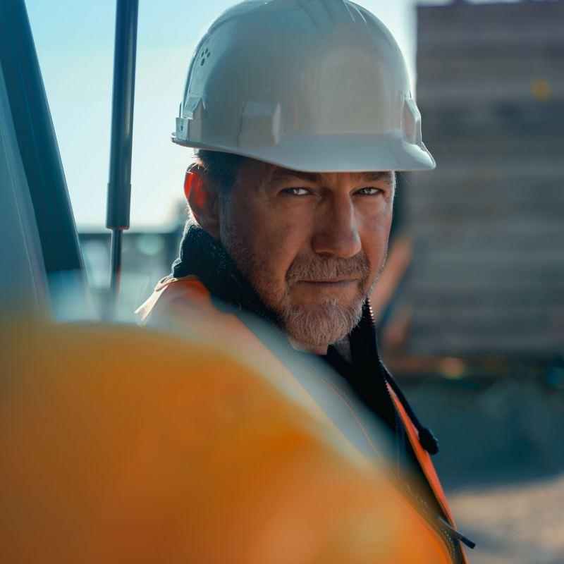 Ein Bauarbeiter steht an einem Volkswagen Nutzfahrzeug.
