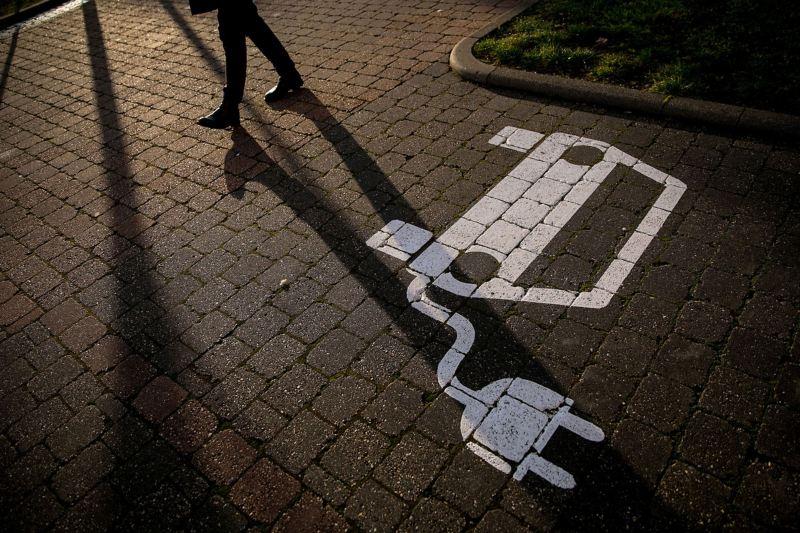 Ein Parkplatz mit einem in weiß gemalten Auto-Symbol und einem Stromstecker