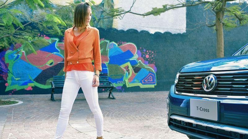 Joven mujer delante de un SUVW T-Cross comprado con plan de financiamiento Volkswagen.