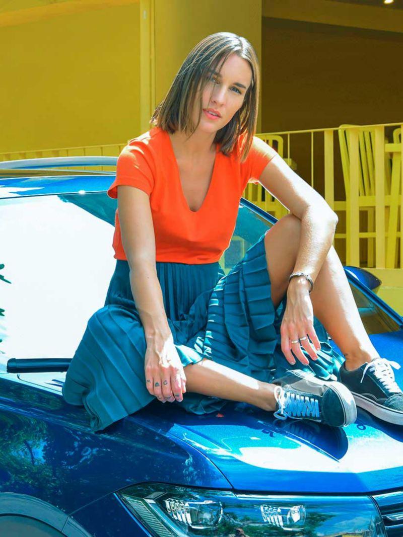 Mujer joven sentada sobre una nueva camioneta que compró con T-Cross Entre Dos.