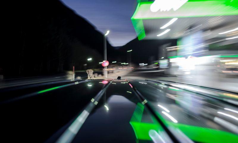 Langzeitbelichtung einer beleuchteten Tankstelle bei Nacht, vom Dach eines fahrenden Autos