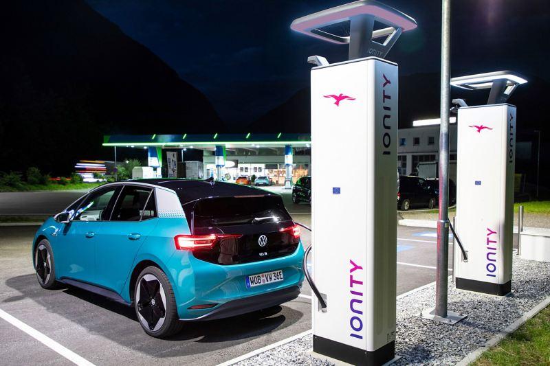 Ein Elektroauto lädt an einer IONITY-Ladesäule, die in der Nähe einer Tankstelle steht