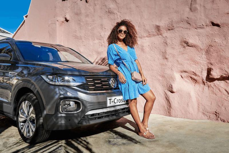 VW - T Cross SUV estacionado un dia soleado con mujer de vestido azul