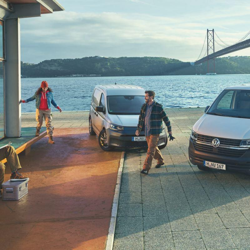 Ein VW Caddy und ein VW Transporter nebeneinander vor einer Hafenkulisse.