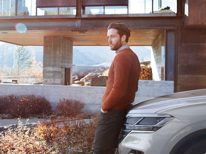 Tengo un Volkswagen - Hombre frente a auto respaldado con Servicios de Servicio Post-Venta