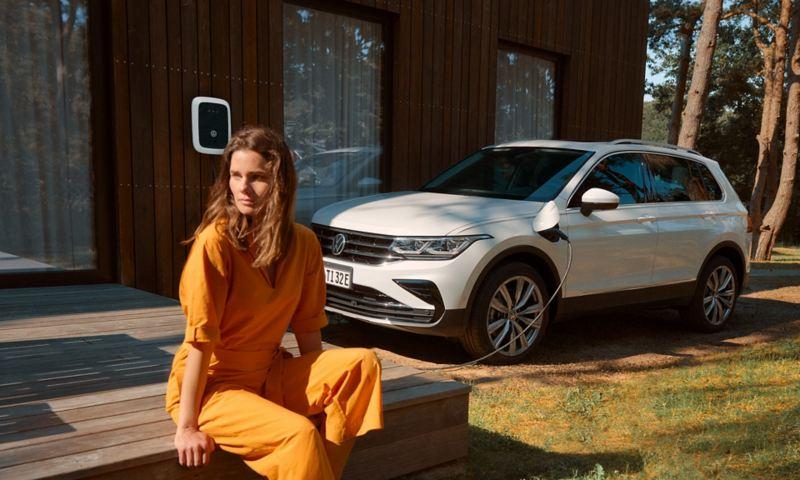 Frau sitzt vor einem VW Tiguan, der an einer Wallbox lädt.