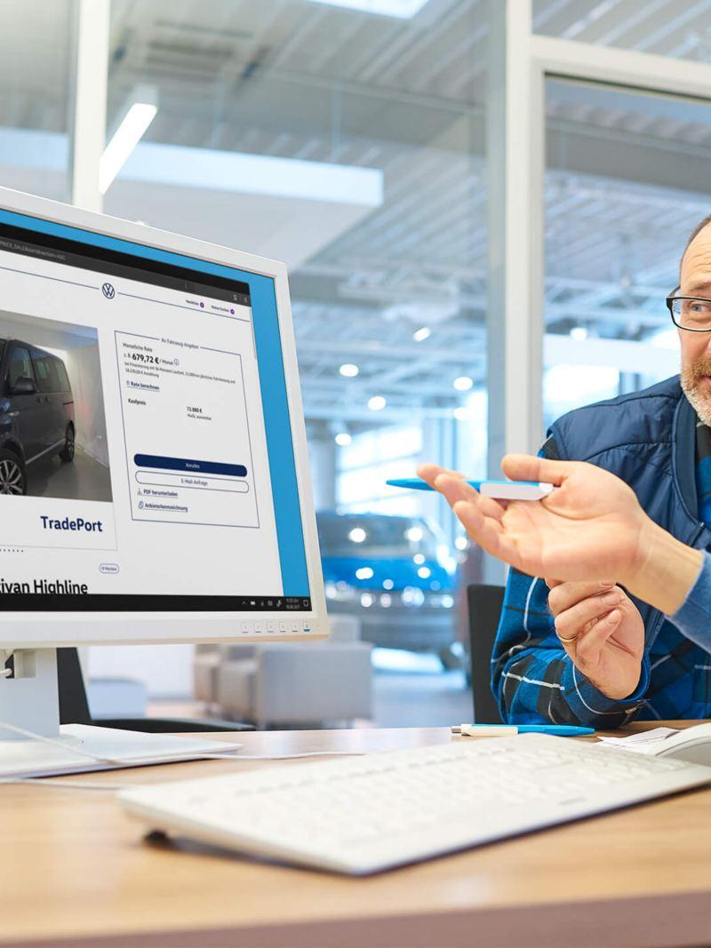 Ein TradePort Mitarbeiter sitzt mit einem Kunden vor einem PC.