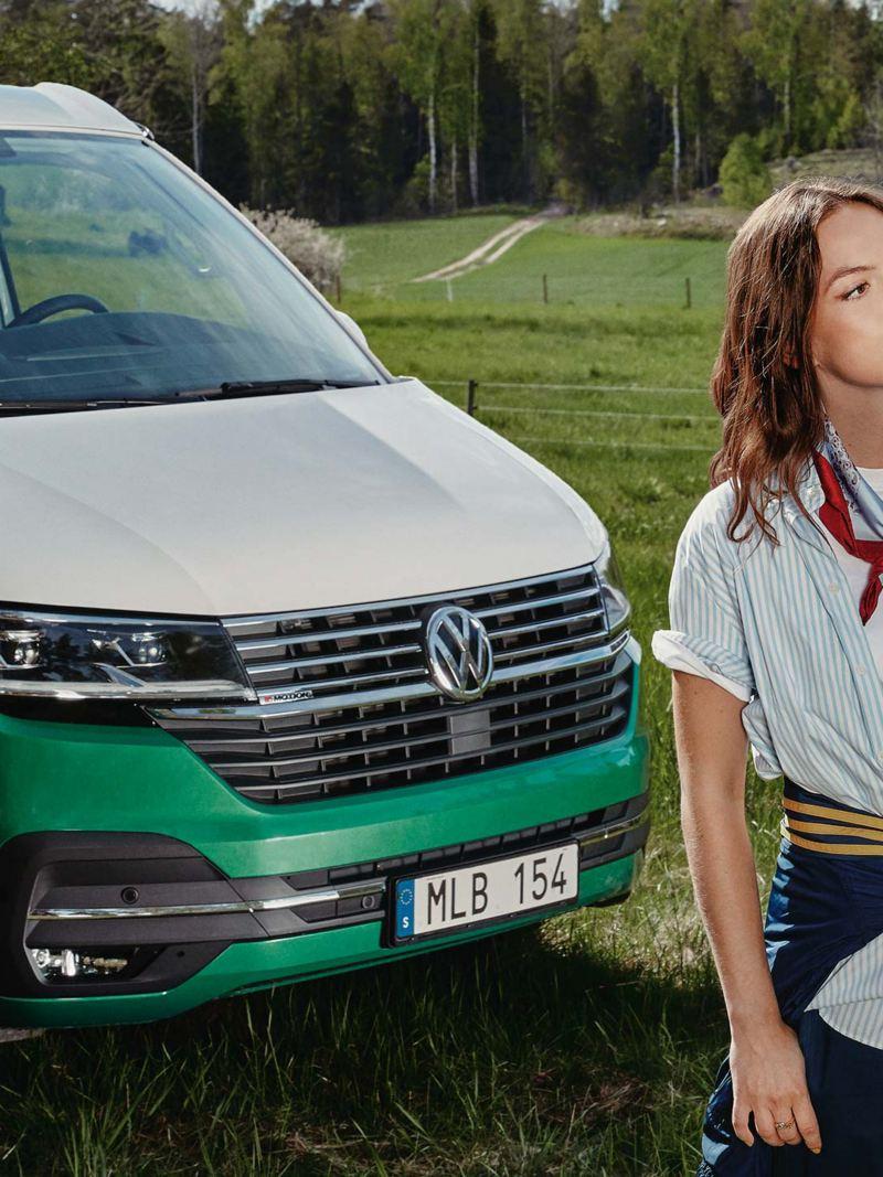 Kvinna står framför en VW California 6.1 campingbil