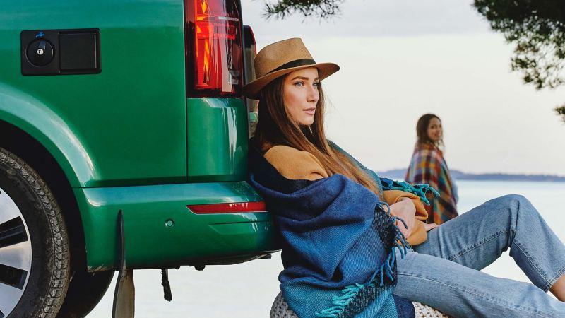 Kvinna sitter på en strand lutandes mot en VW California 6.1 campingbil