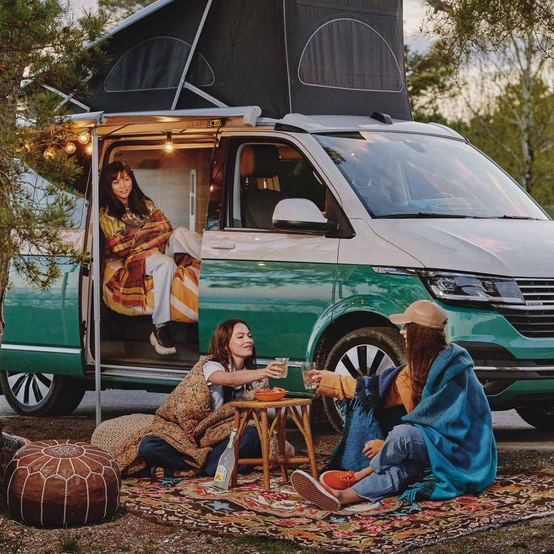 Kvinnor campar utanför en VW California 6.1 campingbil