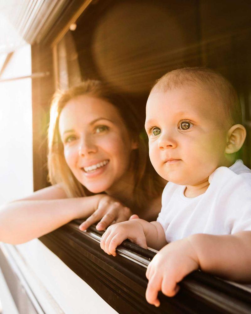 Mutter und Kind schauen aus dem Fenster eines Wohnwagens