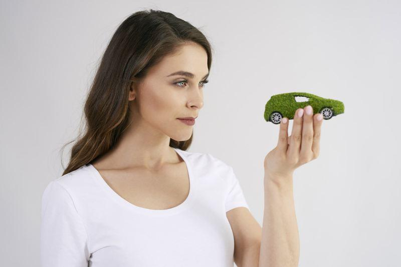 Eine Frau hält ein kleines, grün-bemoostes Modellauto in der Hand und schaut es sich an
