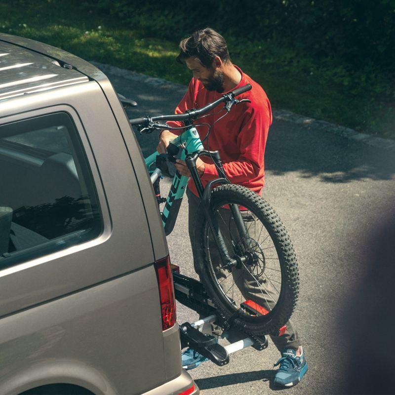 Mann hängt sein Fahrrad am Fahrradträger auf
