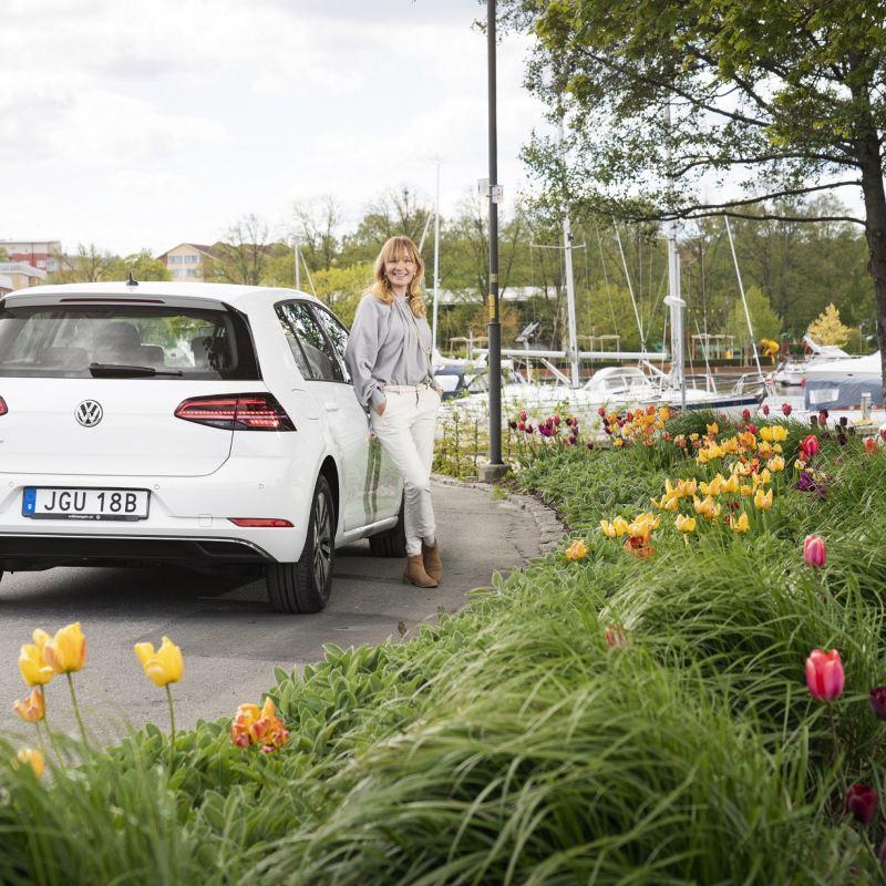 Kvinna står lutad mot Volkswagen e-Golf