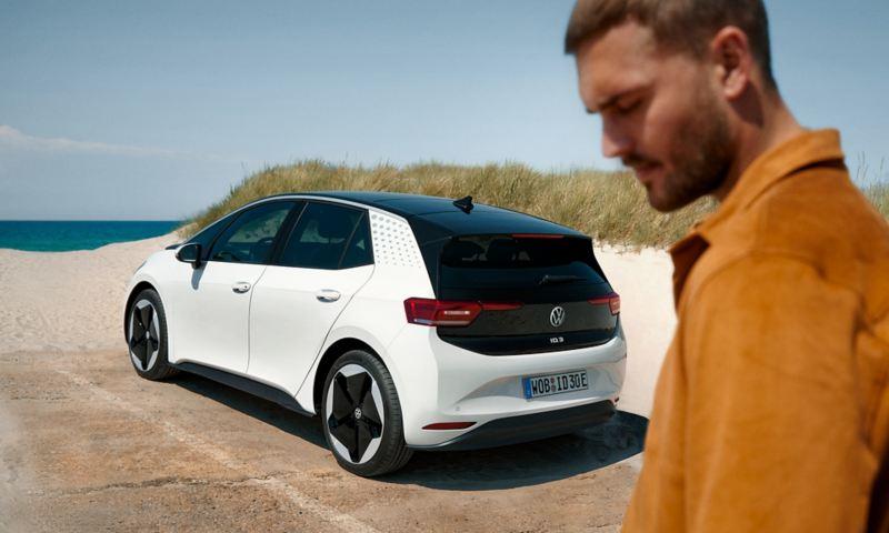 Ένας άνδρας στην παραλία, πίσω του το Volkswagen ID.3.