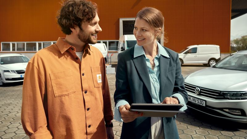 Zwei Personen stehen vor einer Flotte von VW Modellen.