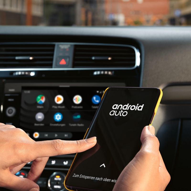 Driver inside a Golf looking at the Android Auto app on a smartphone