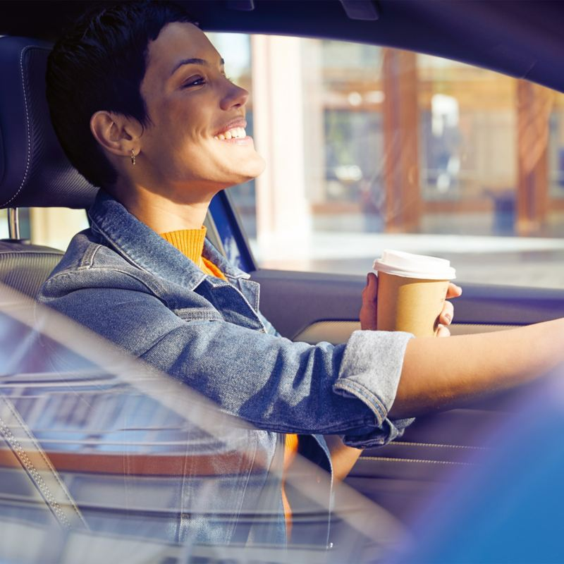 Lady in her car with a coffee