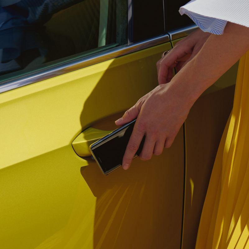 Lady using her mobile key to unlock her car