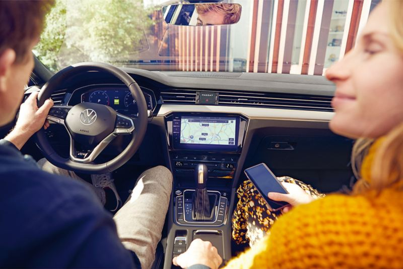 A couple sitting inside a VW car with the woman holding a mobile phone