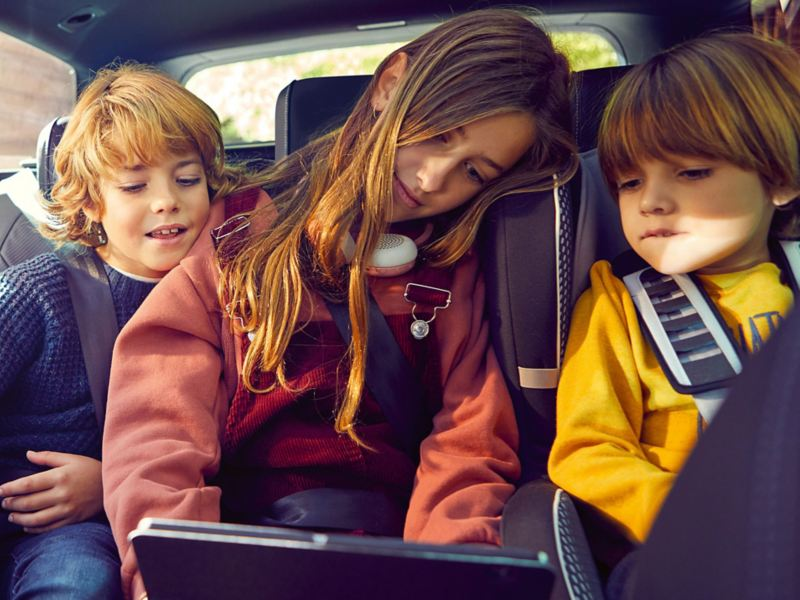 Kids sat on the back seat of a VW and using the We Connect services