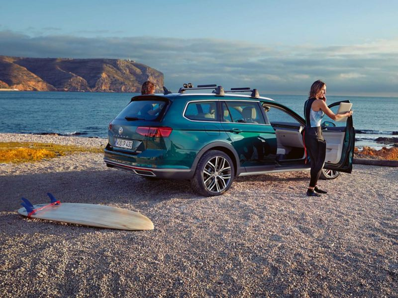 Woman in surf gear standing outside of a Passat Alltrack on the beach