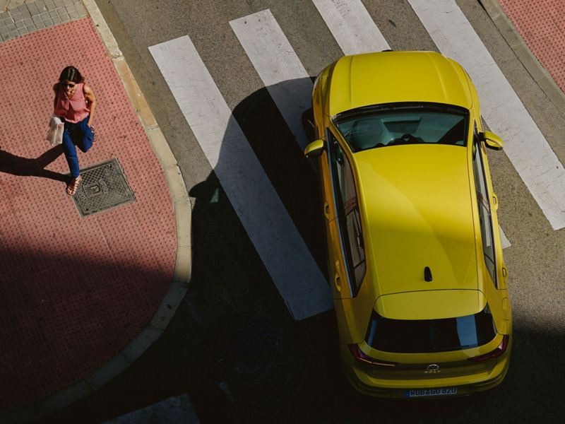 A woman walking past a yellow Passat car in the street