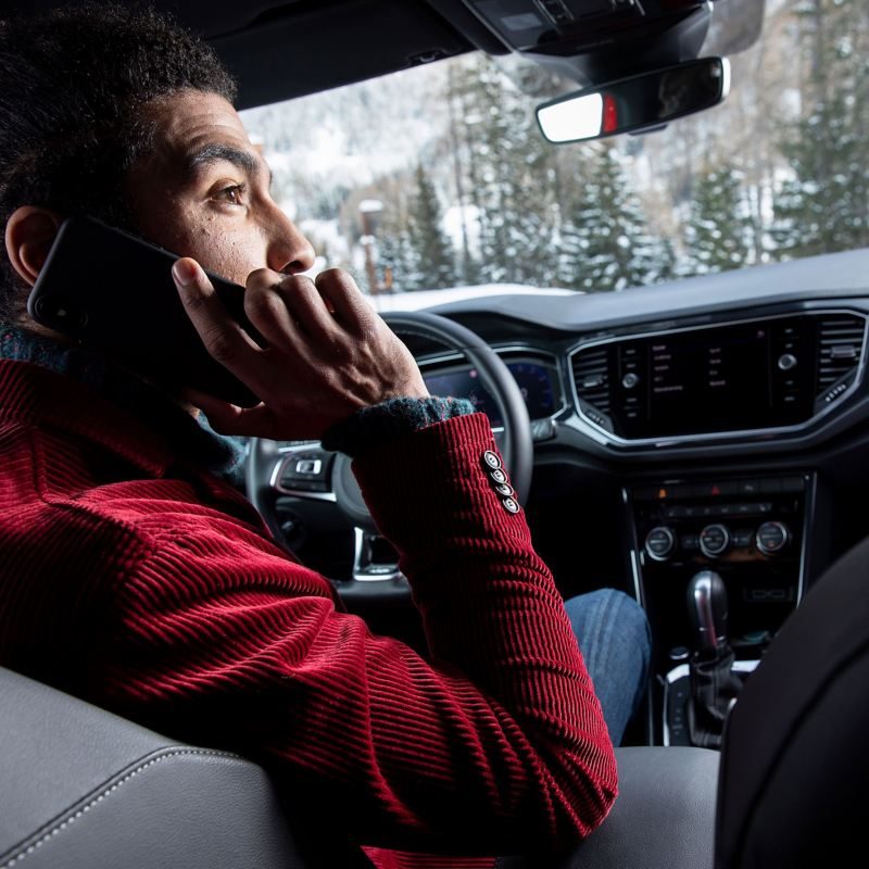 A man making a mobile phone call at the wheel of a Volkswagen car