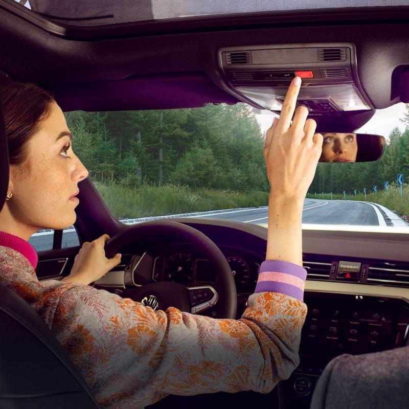 A woman sat inside her car touching buttons