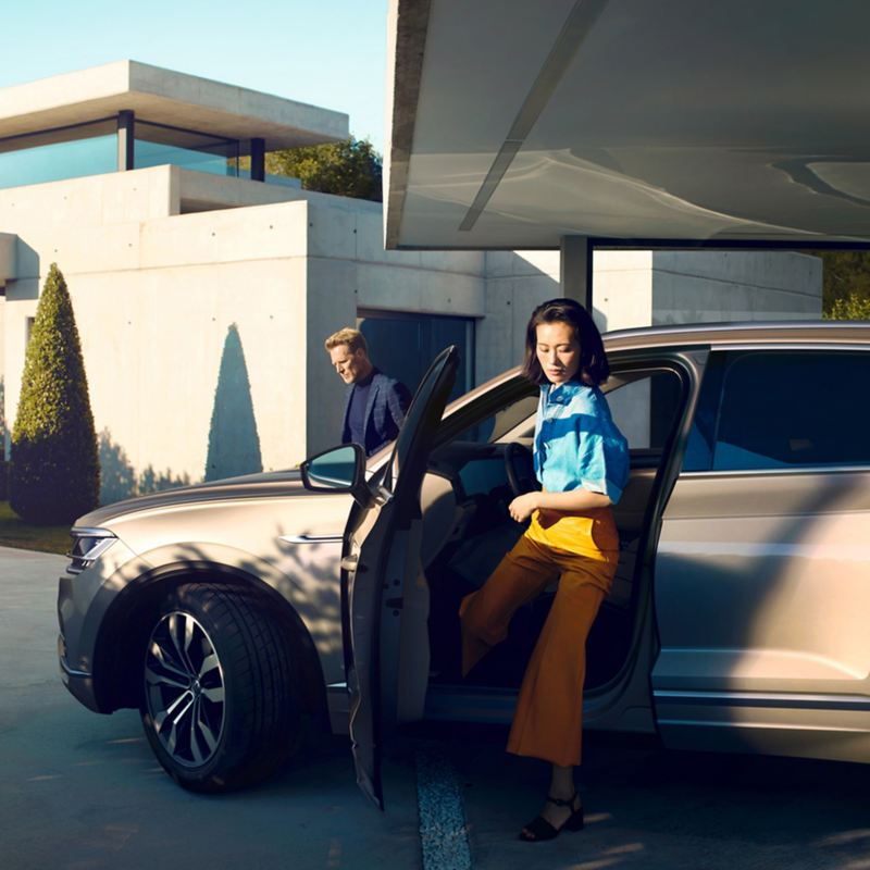 A woman stepping out of a Volkswagen car